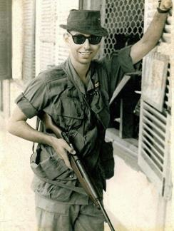 Louis Galanos with his M2 Carbine in front of the classified documents office at the United States Army Support Command in Qui Nhon.