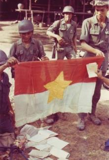 ARVN infantrymen display propaganda leaflets and a flag captured by them during a drive against Viet Cong guerrillas.