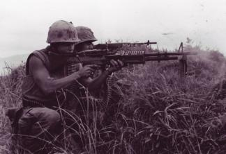 A machine gunner and a rifleman from the 5th Marine Regiment fire at the enemy near the DMZ in Vietnam.