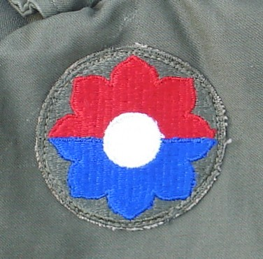 The shoulder sleeve insignia of the 9th Infantry Division was an octofoil horizontally divided into red and blue halves.